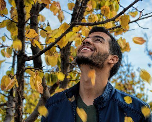 Man With Blue Denim Zip-up Jacket Near Yellow Leaf Tree