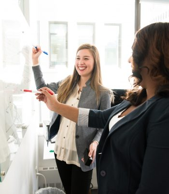 Canva - Two Women in Front of Dry-erase Board
